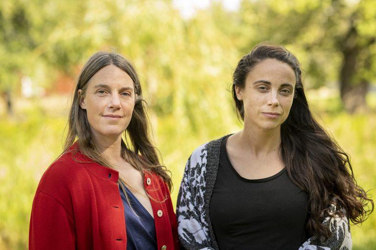 Två kvinnor tittar in i kameran. Sommargrönska i bakgrunden.