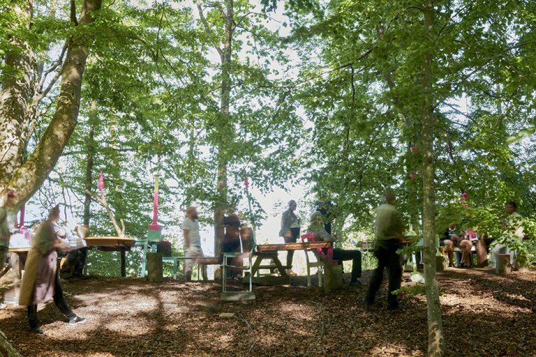 I en glänta i skogen, bland skir grönska, går människor i ett konstverk