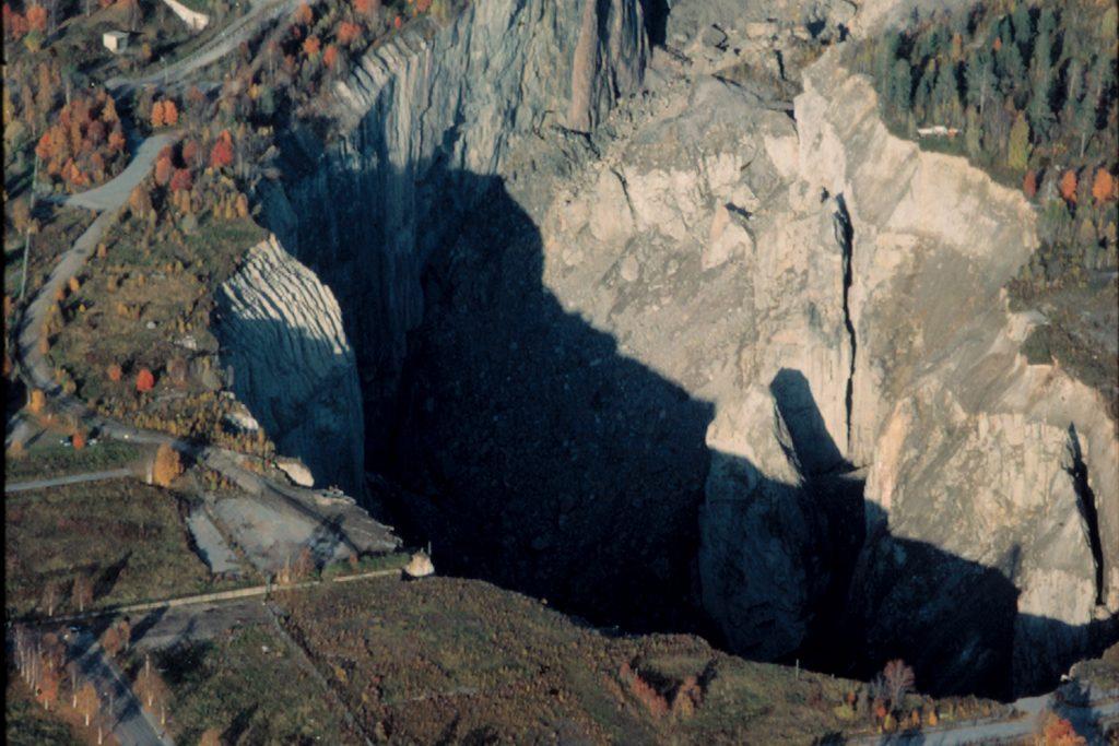Ett djupt gruvschakt sett från luften med hus vid sidan av kanten.