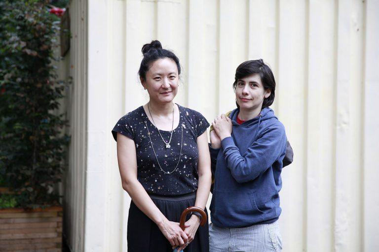 Två kvinnor framför en vit husvägg
