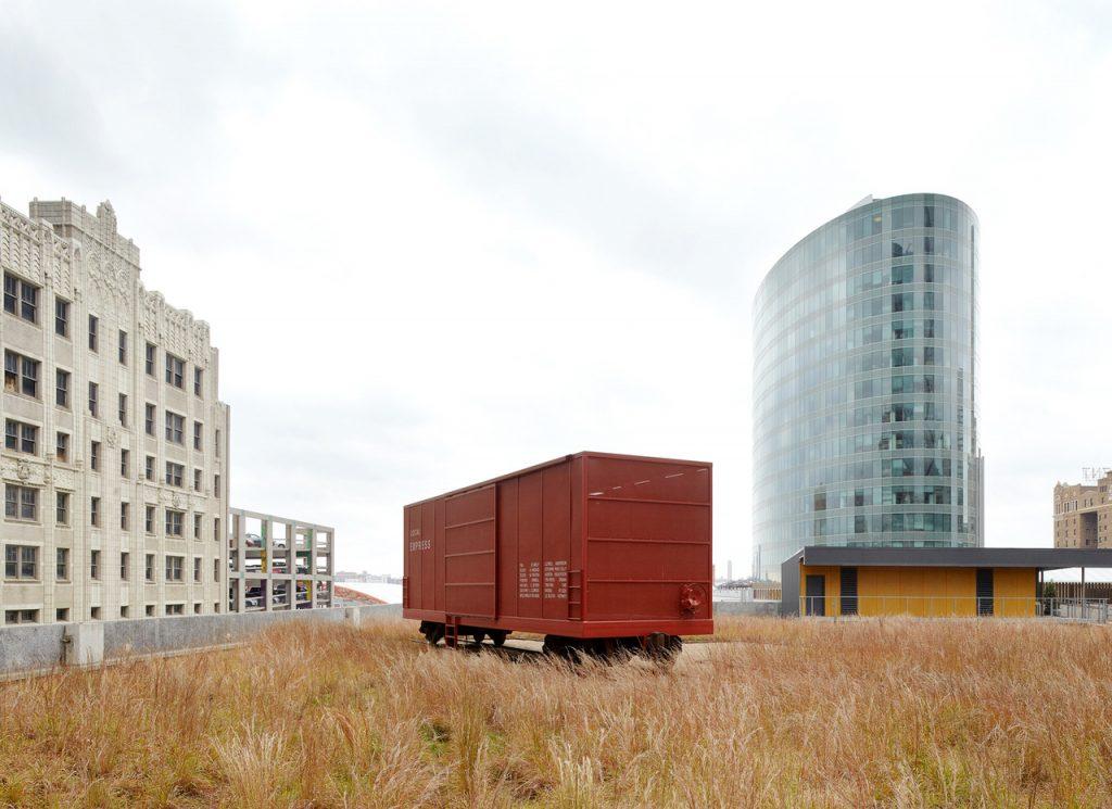 En röd godsvagn står bland högt gräs, i bakgrunder syns en låg skyskrapa och ett äldre hus