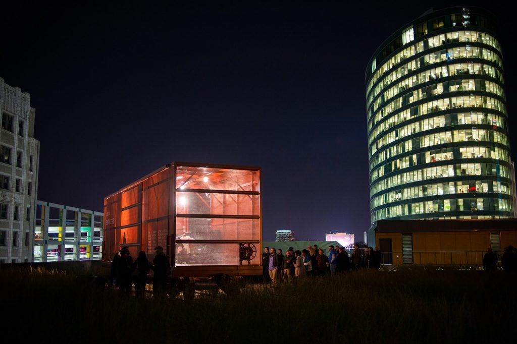 Bild tagen på natten av upplyst röd godsvagn i gräs framför en skyskrapa
