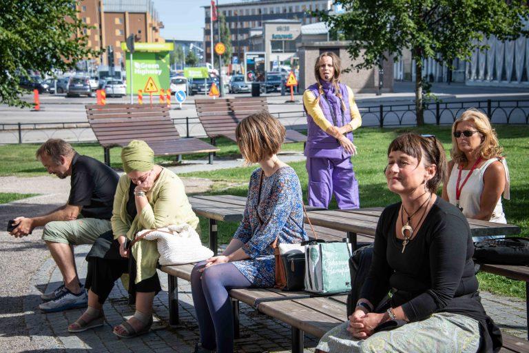 Människor som sitter på bänkar i torg i stad.