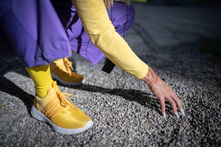 Konstnärens fot och hand mot marken. Handen är sminkad som en hund.