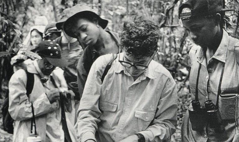 En svartvit bild där en grupp män ser ut att arbeta med något i en trädgård.
