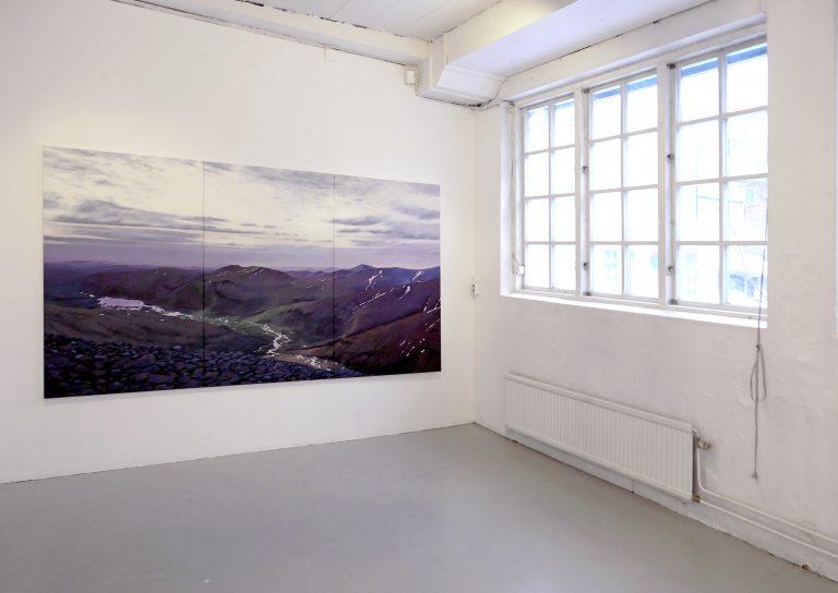 Tomt rum där en stor tavla med landskap hänger bredvid stora fönster.