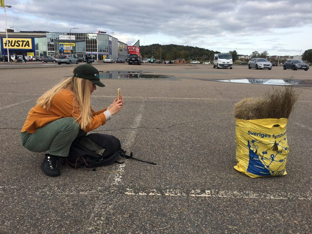 Kvinna hukar på en parkeringsplats och fotar en kassa med lin