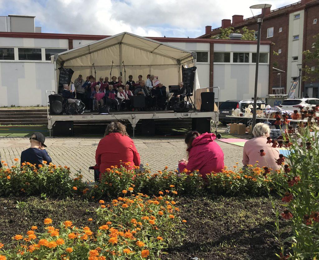 Fyra personer sitter framför en rabatt och tittar mot en scen. På scenen spelar en orkester.