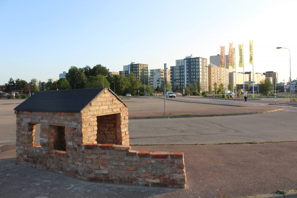 Litet hus av tegel på stor parkeringsplats