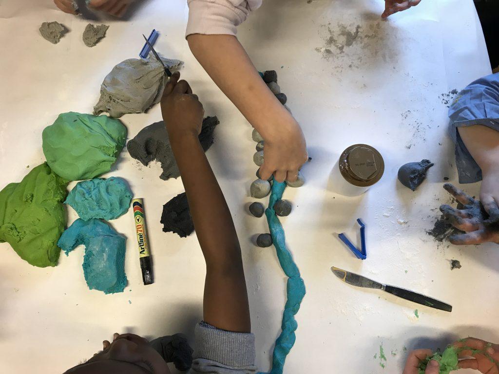 Händer arbetar med lera i olika färger och bygger landskap på ett bord.