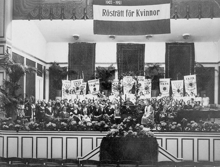 En svartvit bild på en scen. På scenen finns flaggor i bakgrunden och sittande kvinnor längre fram. En kvinna står vid en talarstor. Ovan scenen finns en flagga där det står Rösträtt för kvinnor.