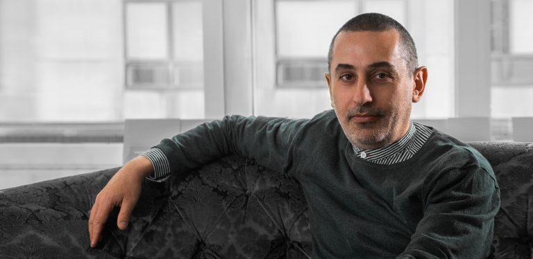 En man sitter lutad mot en soffa. Han tittar rakt in i kameran. Fönster i bakgrunden.
