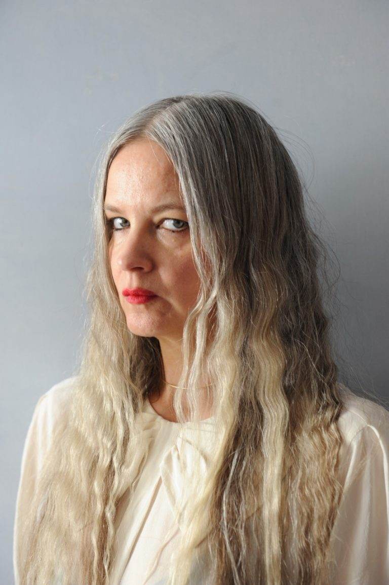 Porträtt på en kvinna mot en grå bakgrund.