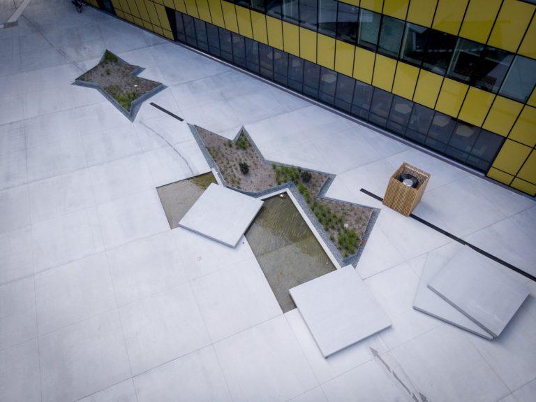 Närbild på torg där några några betongplattor lyfts upp och vatten finns under.
