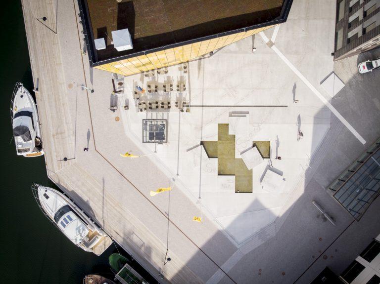 Bild på torg sett ovanifrån. Höger om torget syns båtar och vatten. Mitt på torget är stenplattor bortplockade och vatten syns. Konturer av ett skepp syns svagt i betongen-
