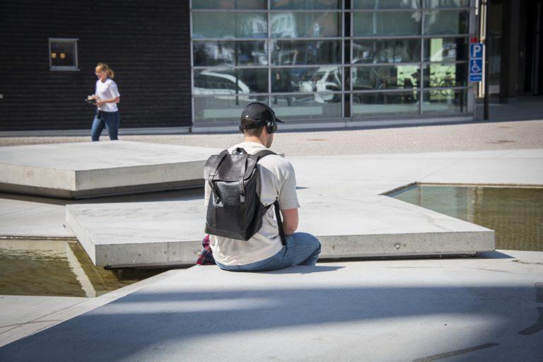 En person sitter på betongplatta. i Bakgrunder finns fler plattor och vatten.