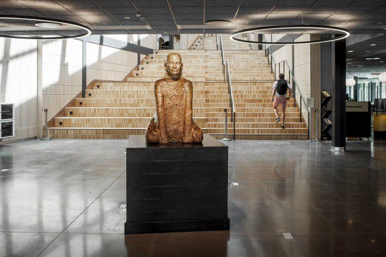 I en entré, framför en bred trappa, finns en träskulptur som består av en sittande man.