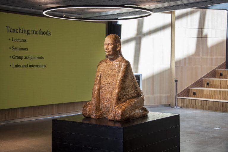 I en entré, på en sockel, står en träskulptur som består av en sittande man.
