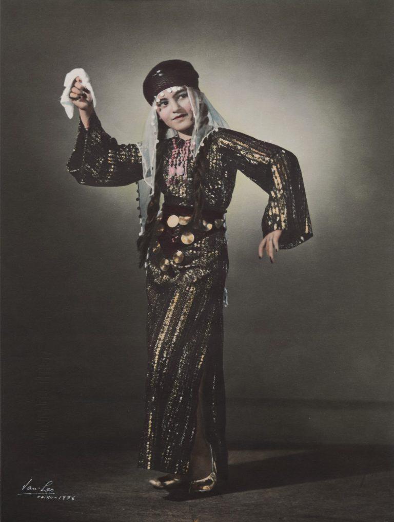 En kvinna i klänning och huvudbonad dansar med en näsduk