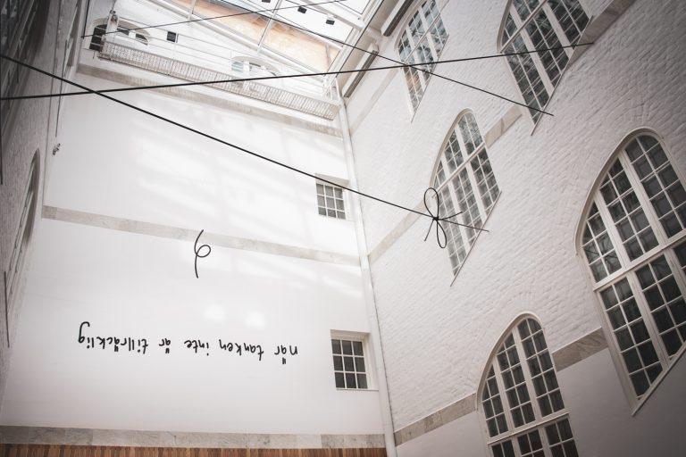En innergård med glastak. På väggen finns bokstäver och svarta linjer syns ii luften genom rummet.